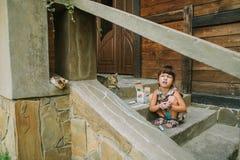 Dziewczyna rysuje kredę blisko drewnianego domu Fotografia Stock