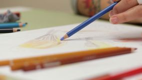 Dziewczyna rysuje leworęcznego z błękitnym ołówkiem na papierze, szczegółowy widok w slowmotion zdjęcie wideo