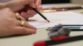 Dziewczyna rysuje leworęcznego z barwionym ołówkiem na papierze, szczegółowy widok w slowmotion zbiory