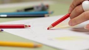 Dziewczyna rysuje leworęcznego z czerwonym ołówkiem na papierze, szczegółowy widok w slowmotion zbiory