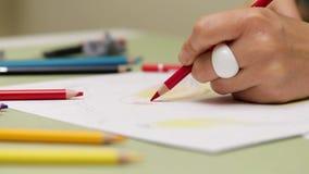 Dziewczyna rysuje leworęcznego z czerwonym ołówkiem na papierze, szczegółowy widok w slowmotion zbiory wideo