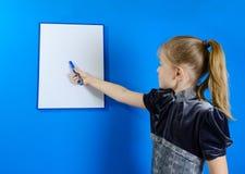 Dziewczyna rysuje na białej klingeryt desce Zdjęcie Stock