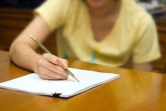 Dziewczyna rysuje na stosie papier Zdjęcia Royalty Free