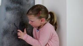 Dziewczyna rysuje palec na nadokiennej tafli Śliczna mała dziewczyna wyciera zamarzniętego okno w zima czasie zbiory wideo