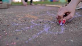 Dziewczyna rysuje z barwioną kredą na asfalcie W górę ręk z kredą dobry humor Rozrywka i odpoczynek zbiory wideo