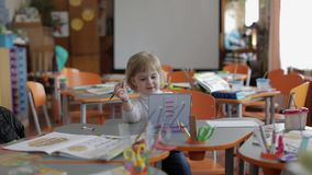 Dziewczyna rysunek przy stołem w sali lekcyjnej Edukacja Dziecka obsiadanie przy biurkiem zdjęcie wideo