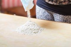 Dziewczyna rzuca mąkę na stole obraz royalty free