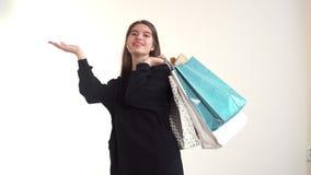Dziewczyna rzuca torby na ona z powrotem z jeden ręką, i drugi pokazuje obok one palmowi z zdjęcie wideo