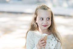 Dziewczyna słodki ząb na rozochoconej twarzy je lody, lekki tło Dzieciak dziewczyna z lody rożkiem w ręce Słodki ząb Zdjęcia Royalty Free