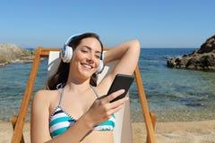 Dziewczyna słucha muzyczny obsiadanie na hamaku na plaży zdjęcia stock