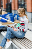 Dziewczyna słucha muzykę podczas gdy siedzący na ławce przy szkołą wyższa Zdjęcia Stock