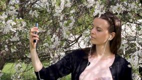 Dziewczyna słucha muzyka i bierze selfie w kwitnienie ogródzie zdjęcie wideo