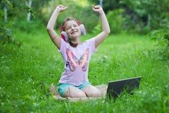 Dziewczyna słucha muzyka na hełmofonach outdoors Obrazy Stock