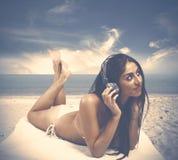 Dziewczyna słucha muzyka przy plażą fotografia stock