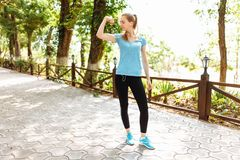 Dziewczyna słucha muzyka w hełmofonach podczas szkolenia, biega w świeżym powietrzu, ranku szkolenie zdjęcie stock