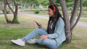 Dziewczyna słucha muzyka w hełmofonach siedzi blisko drzewa w parku zbiory wideo