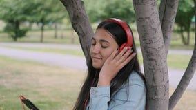 Dziewczyna słucha muzyka w hełmofonach siedzi blisko drzewa w parku Zako?czenie zbiory wideo