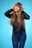 Dziewczyna słucha muzyka z dużymi czerwonymi hełmofonami Zdjęcie Stock