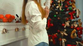 Dziewczyna słucha muzyka z hełmofonami i dekoruje choinki zbiory wideo