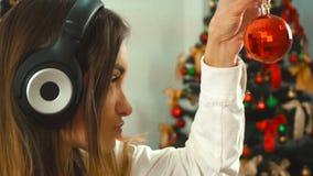 Dziewczyna słucha muzyka z hełmofonami i dekoruje choinki zbiory