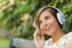 Dziewczyna słucha muzyka z hełmofonami w parku Zdjęcie Royalty Free