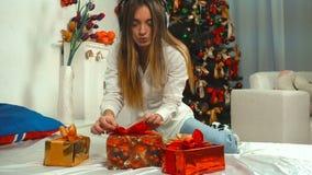 Dziewczyna słucha muzyka z hełmofonami z wiązką Bożenarodzeniowi prezenty na łóżku zbiory