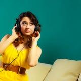 Dziewczyna słucha muzyki mp3 relaksować w dużych hełmofonach Obraz Royalty Free