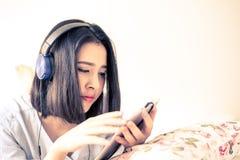 Dziewczyna słucha używać hełmofon i telefon komórkowego Fotografia Stock