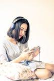 Dziewczyna słucha używać hełmofon i telefon komórkowego Obrazy Stock