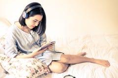 Dziewczyna słucha używać hełmofon i telefon komórkowego Zdjęcie Stock