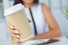 Dziewczyna seansu papieru filiżanka kawy w jego rękach zamyka up Amerykanina eco papierowa filiżanka Dziewczyna pije kawę indoors fotografia royalty free