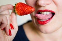 Dziewczyna seksualnie liże truskawkowej jagody z jej jęzorem zdjęcia royalty free