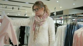 Dziewczyna shopaholic robi zakupom, rozmaitości i mannequins w odzieży kobiety odzieżowa sprzedaż, rzeczy wiesza na wieszakach zdjęcie wideo