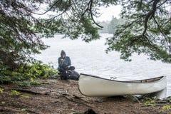 Dziewczyna siedzi białego pustego miejsca czółno parkował wyspę podczas deszczowego dnia w Kanada Ontario jeziora dwa rzek Algonq Zdjęcia Stock