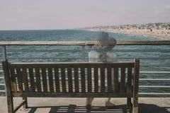 Dziewczyna Siedzi i Kontempluje na ławce z widok na ocean fotografia stock
