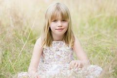 dziewczyna siedzi młody na zewnątrz zdjęcia stock
