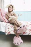 Dziewczyna Siedzi Na łóżku W królika potwora I kostiumu kapciach Obrazy Royalty Free