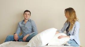 Dziewczyna siedzi na łóżku w sypialni pyta faceta bawić się z poduszkami zbiory
