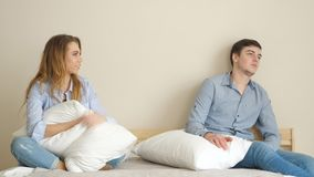 Dziewczyna siedzi na łóżku w sypialni pyta faceta bawić się z poduszkami zdjęcie wideo
