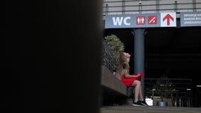 Dziewczyna siedzi na ławce i trzyma jej oddech więc no urinate podczas gdy czekający kolejkę dla zbiory wideo