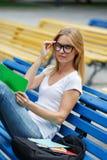 Dziewczyna siedzi na ławce przystosowywa szkła Obraz Royalty Free
