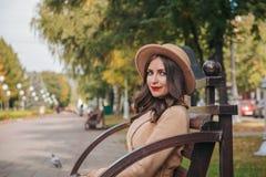 Dziewczyna siedzi na ławce z czerwonymi wargami Obrazy Stock