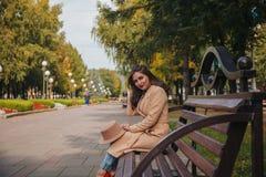 Dziewczyna siedzi na ławce z czerwonymi wargami Zdjęcia Royalty Free