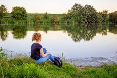 Dziewczyna siedzi na banku rzeka i kontempluje kawalera obrazy stock