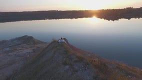 Dziewczyna siedzi na brzeg jezioro zbiory wideo