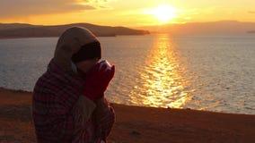 Dziewczyna siedzi na brzeg morze i pije gorącej herbaty Piękny złoty zmierzch zdjęcie wideo
