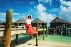 Dziewczyna siedzi na drewnianym moście blisko pensjonatów podczas wakacji Maldives, Lhaviyani atol - zdjęcie royalty free