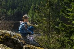 Dziewczyna siedzi na falezie i spojrzeniach przy naturą, dziewczyny obsiadaniem na skale i cieszyć się dolinnego widok, fotografia stock
