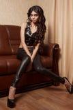 Dziewczyna siedzi na kanapie w czarnej skórze odzieżowej i piętach zdjęcia stock