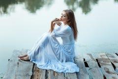 Dziewczyna siedzi na nabrzeżu zanudzającym z dużymi oczami Zdjęcia Royalty Free